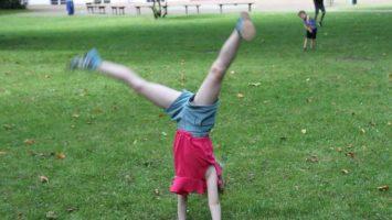 Einzelkinder: Ratschlagendes Kind auf einem Rasen mit einem weiteren Kind im Hintergrund